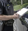 Policeman writing speeding ticket.